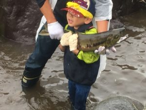 鮭をしっかりと抱く男の子